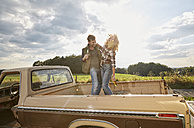 Happy couple standing on pick up truck with beer bottles - FMKF03165