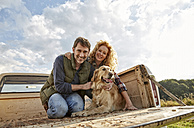 Happy couple with dog on pick up truck - FMKF03168