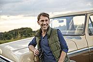 Smiling man at pick up truck holding binoculars - FMKF03177