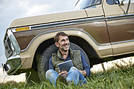 Smiling man sitting at pick up truck with tablet - FMKF03180