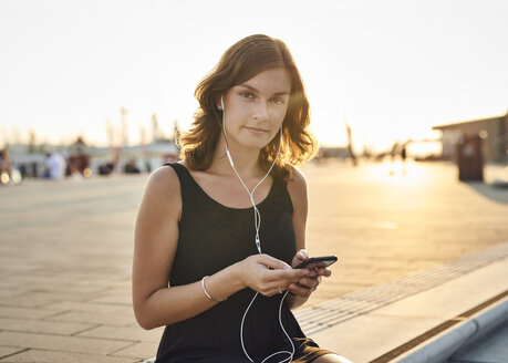 Germany, Young woman with smart phone exploring Hamburg - WHF00002