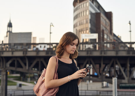 Germany, Young woman with smart phone exploring Hamburg - WHF00011