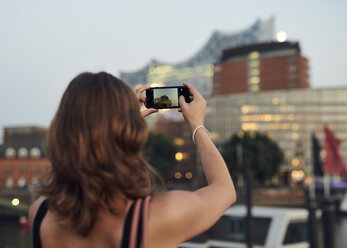 Germany, Young woman in Hamburg taking pictures with her smart phone - WHF00017