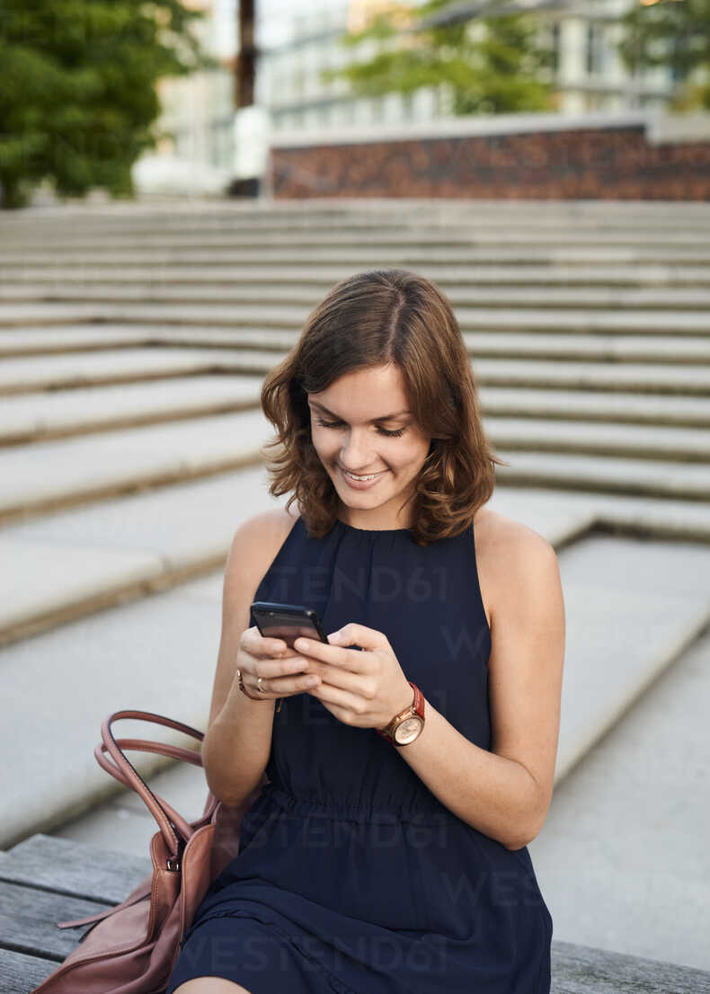 Germany, Young woman in Hamburg using smart phone - WHF00029 - Wiho/Westend61