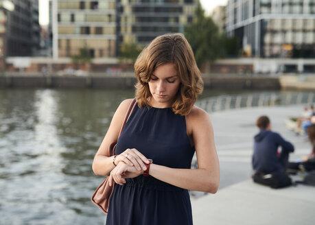 Germany, Hamburg, Young woman looking at watch - WHF00032