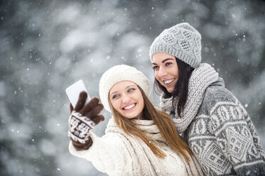 Portrait of two friends taking selfie with smartphone in winter - HHF05467