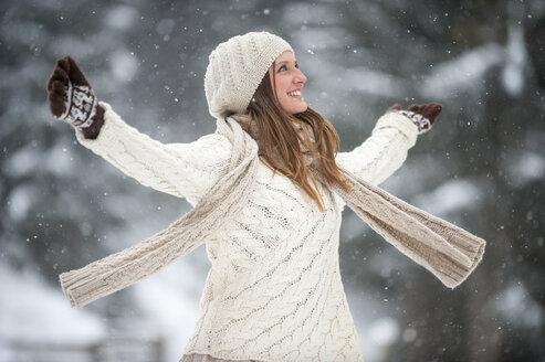 Happy blond woman wearing knitwear in winter - HHF05473