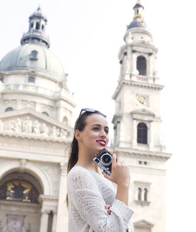 Hungary, Budapest, young woman with camera in front of St. Stephen's Basilica - JLRF00083