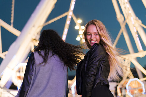 Two happy young women on a funfair at night - KKAF00036