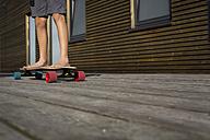 Legs of boy standing on his skateboard - JTLF00121