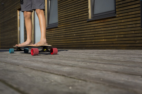 Legs of boy standing on his skateboard - JTLF00121