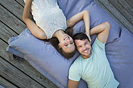 Young couple in love relaxing together on beanbag - JTLF00124