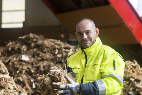 Portrait of content worker at wood recycling yard - SGF02068