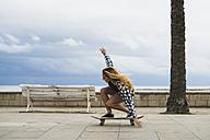 Young woman balancing on skateboard - KKAF00044
