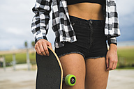 Woman with skateboard wearing black Hot Pants, partial view - KKAF00047