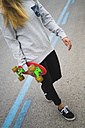 Young woman with skateboard crossing the street - KKAF00056