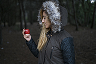 Young woman with red apple wearing hooded jacket - KKAF00065