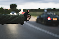 Hand of hitchhiking young woman waiting at roadside in the evening - KKAF00071