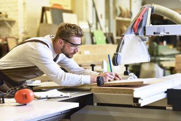 Carpenter measuring wooden boards in his workshop - LYF00658
