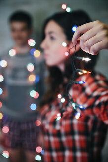 Hand of woman holding fairy lights - RTBF00516