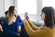 Young woman taking a smartphone picture of female friend - LCUF00080