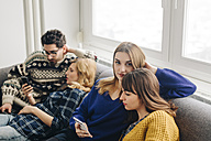 Four friends with smartphones on couch in living room hanging out - LCUF00083