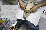 Shoemaker putting the sole on a shoe in his workshop - ABZF01468