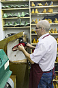 Shoemaker using a machine in his workshop - ABZF01474