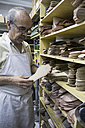 Shoemaker selecting shoe soles from a shelf in his workshop - ABZF01483