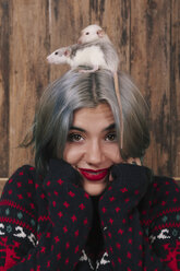 Portrait of smiling young woman with two pet rats on her head wearing patterned knit pullover - RTBF00523