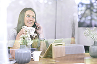 Smiling young woman at home using cell phone and tablet - MADF01180