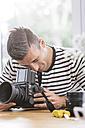 Man at home checking camera - MADF01195