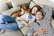 Smiling couple with dog lying on couch - MADF01198