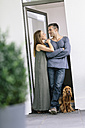 Smiling couple with dog standing at terrace door - MADF01204