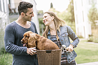 Smiling couple with dog in bicycle basket - MADF01213