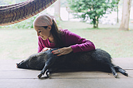 Peru, Woman cuddling domesticated peccary - GEMF01218