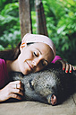 Peru, Woman cuddling domesticated peccary - GEMF01221