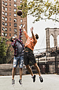 USA, New York, two young men playing basketball on an outdoor court - UUF09127
