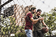 Two smiling friends with basketball and cell phone outdoors - UUF09139