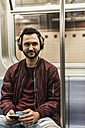 Young man sitting in subway wearing headphones - UUF09157