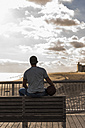 USA, New York City, man sitting on bridge on Coney Island with basketball - UUF09169