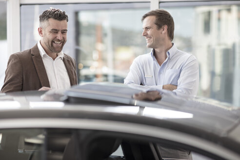 Car showing car to happy customer at car dealership - ZEF11532