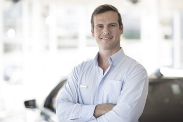 Portrait of confident car dealer in showroom - ZEF11538