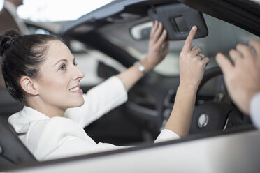 Smiling woman sitting in car at car dealership - ZEF11544