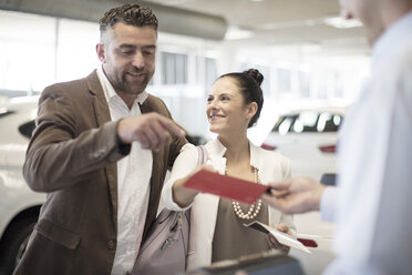 Couple choosing from color sample at car dealership - ZEF11550
