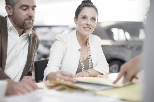 Car dealer and couple sitting at desk with agreement forms in showroom - ZEF11553