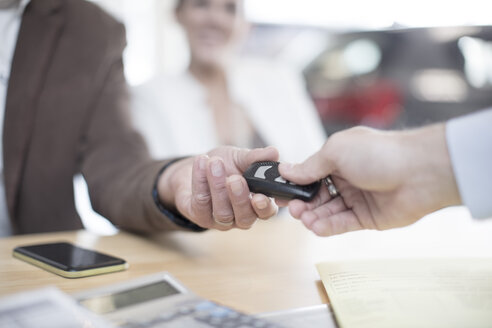 Car dealer handing over key to man at car dealership - ZEF11556