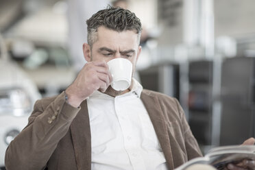 Man drinking coffee reading magazine at car dealership - ZEF11559