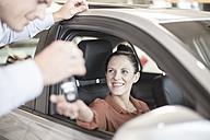 Car dealer handing over key to woman at car dealership - ZEF11568