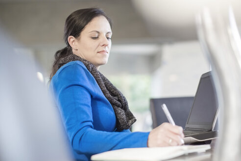 Woman at desk with laptop writing in notebook - ZEF11580